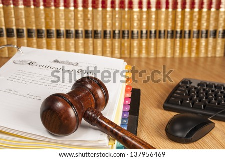 Justice gavel on certificate of title with legal books and computer keyboard in the background - stock photo