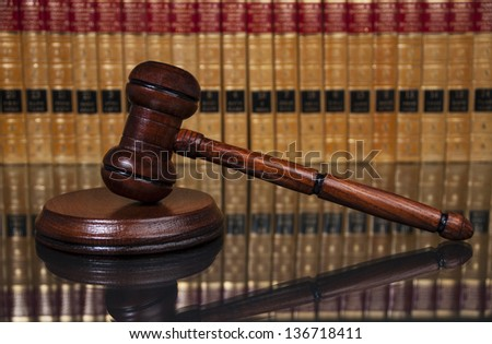 Justice gavel with old books in the background - stock photo
