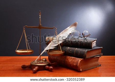 Justice or science still life. Old brass weight scale near books and feather on dark background - stock photo