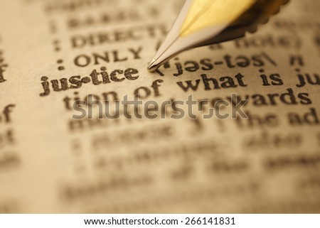 Justice pen nib pointing to the words in the dictionary, shot with very shallow depth of field, - stock photo