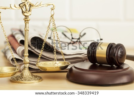 Justice scale with gavel, newspaper and eyeglasses