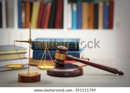Justice scales with gavel and stack of books on wooden table - stock photo