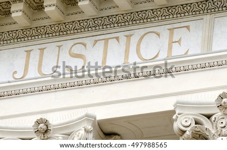 justice word set in stone on an old court