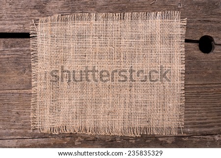 Jute canvas background on wooden board - stock photo