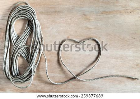 jute rope in heart shaped  wood board - stock photo