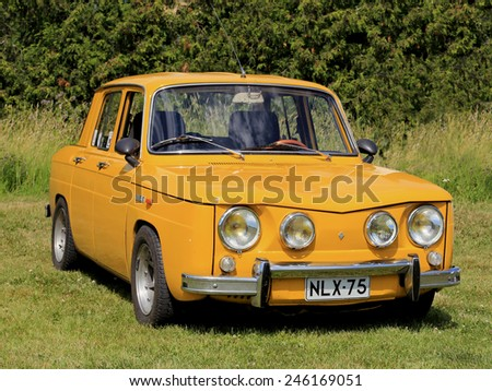 KAARINA, FINLAND - JULY 19, 2014: Yellow Renault 8S parked on grass. The Renault 8 is a small family car produced by the French car manufacturer Renault in 1962-1973.  - stock photo