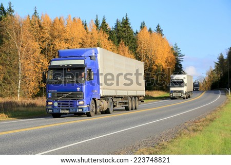 KAARINA, FINLAND - OCTOBER 4, 2014: Three Volvo FH12 trucks are driven in a platoon. The advantages of platooning include greater fuel economy due to reduced air resistance. - stock photo