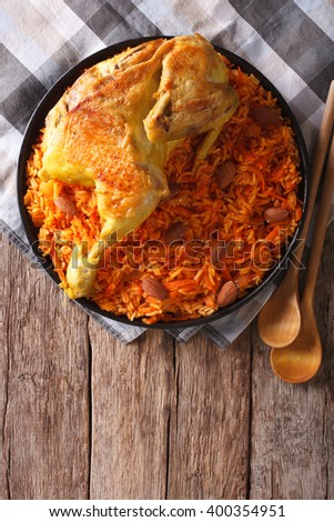 Kabsa of chicken with rice and vegetables on a plate on the table. vertical view from above