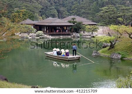KAGAWA, JAPAN - April 10, 2016: The small tourist ship of the pond of Riturin Park Garden in Takamatu, Kagawa, Japan. Tourists are enjoying sightseeing.  - stock photo