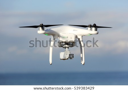 KAGAWA, JAPAN - DECEMBER 15, 2016: White remote controlled Drone Dji Phantom 3 equipped with high resolution video camera hovering in air with shore and?sky