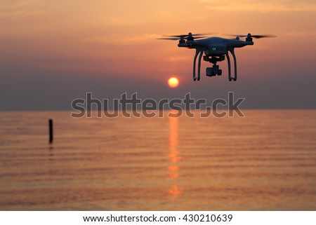 KAGAWA, JAPAN - MAY 31, 2016: Remote controlled drone Dji Phantom 3 equipped with high resolution video camera flying above the sea against a sunset sky. - stock photo