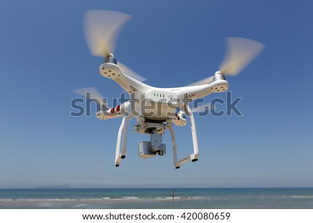 KAGAWA JAPAN - MAY 06, 2016: White remote controlled Drone Dji Phantom 3 equipped with high resolution video camera hovering in air with beach and clear blue sky in the background - stock photo