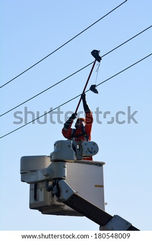 KAITIA, NZ - MAR 06:Electric engineer remove an old shoes from power line on Mar 06 2014.Shoe tossing is a common youth vandalism act of throwing a pair of shoes onto telephone wire or power lines.
