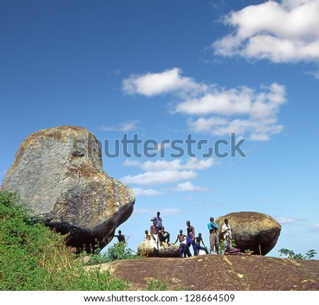 KAKORO ROCK, EASTERN UGANDA - AUGUST 3: Local people at Kakoro rock formation on August 3, 2004 in Uganda. Kakoro rock is known as a place with prehistoric paintings. - stock photo
