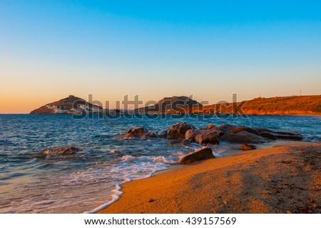 Kalafatis Bay beach on the island of Mykonos at sunrise. Greece. - stock photo