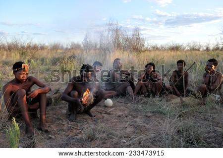 KALAHARI, BOTSWANA - DECEMBER 31, 2008: Bushmen in the desert making fire - stock photo
