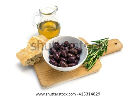 Kalamata black olives in a white bowl, oil, bread and rosemary garnish on a kitchen board, isolated on a white background - stock photo