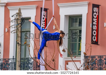 KALAMATA, GREECE - FEBRUARY 2017: Beautiful young woman performing aerial silk dance show in front of neoclassical buildings during the annual Kalamata Carnival event at the main square of the city.