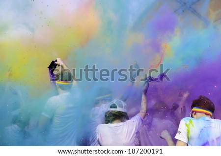 "KALAMAZOO, MICHIGAN, USA - April 12, 2014: Participants celebrate the arrival of spring and the end of a 5K ""fun run"" by creating a multicolored fog of colored powder around themselves. - stock photo"