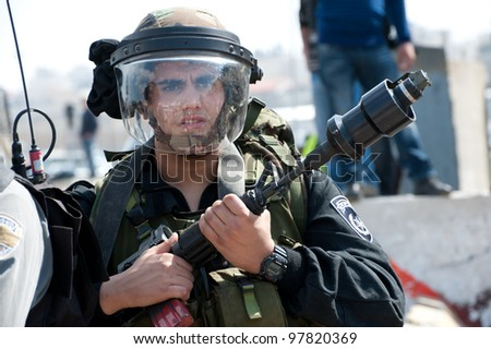 KALANDIA, OCCUPIED PALESTINIAN TERRITORIES - MARCH 8: An Israeli soldier holds a U.S.-made tear gas grenade launcher mounted on an M16 rifle during demonstrations  on March 8, 2012 in Kalandia - stock photo