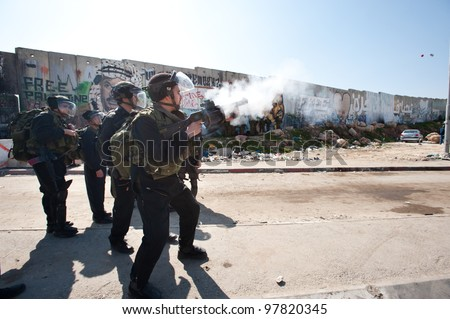 KALANDIA, OCCUPIED PALESTINIAN TERRITORIES - MARCH 8: Israeli soldiers fire tear gas during protests against the occupation of Palestine on March 8, 2012 in Kalandia - stock photo