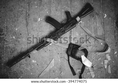 Kalashnikov rifle and a knee on the wooden floor. Black and white