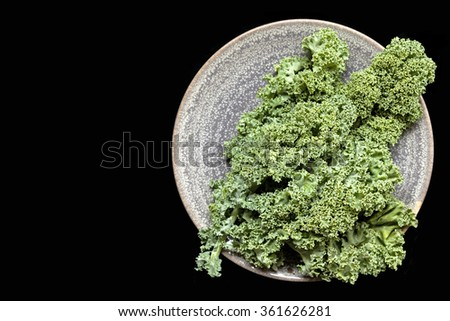 Kale on a rustic plate over black background.  Overhead view, with copy space. - stock photo