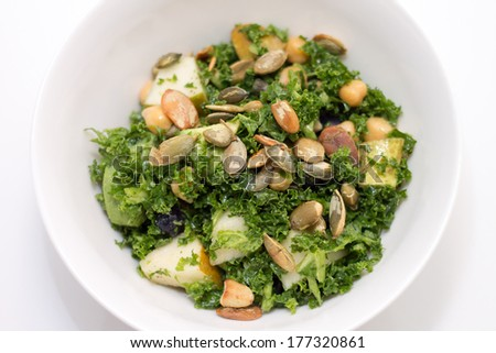 Kale salad with pear, pumpkin seed, blueberry in white bowl on white background - stock photo