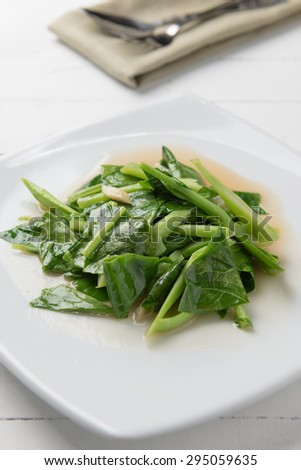Kale stir fried in oyster sauce white plate on white table