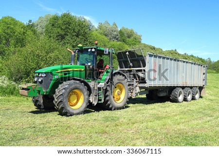 KALININGRAD REGION, RUSSIA - JUNE 11, 2015: The wheel John Deere 7930 tractor with the trailer with a mowed grass in the field - stock photo