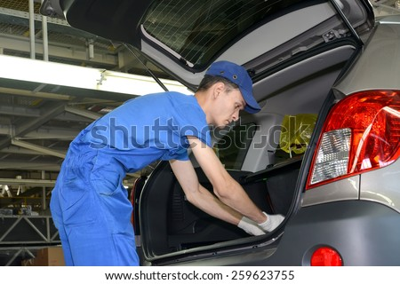 KALININGRAD, RUSSIA - SEPTEMBER 16, 2014: The collector fixes an internal upholstery of a luggage carrier of the car. Assembly shop of automobile plant