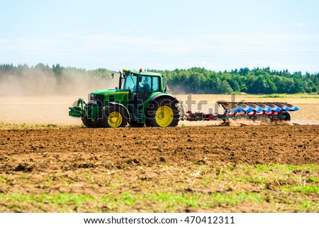Kalmar, Sweden - August 10, 2016: Farmer using a John Deere 6930 while plowing a field after harvest.