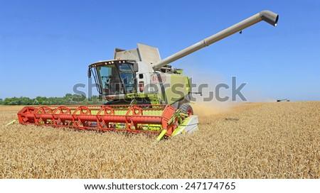 Kalush, Ukraine - AUGUST 7: Modern  combine harvesting grain in the field near the town Kalush, Western Ukraine August 7, 2013  - stock photo