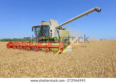 Kalush, Ukraine - AUGUST 7: Modern  combine harvesting grain in the field near the town Kalush, Western Ukraine on August 7, 2014  - stock photo