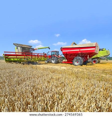Kalush, Ukraine - AUGUST 11: Modern  combines harvesting grain in the field near the town Kalush, Western Ukraine August 11, 2014  - stock photo