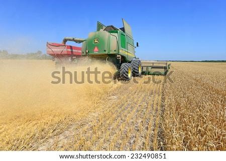 Kalush, Ukraine - AUGUST 7: Modern John Deere combine harvesting grain in the field near the town Kalush, Western Ukraine August 7, 2013  - stock photo
