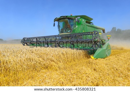 Kalush, Ukraine - AUGUST 8: Modern John Deere combine harvesting grain in the field near the town Kalush, Western Ukraine August 8, 2014