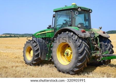 Kalush, Ukraine - August 14: Modern John Deere tractor in the field near the town Kalush, Western Ukraine August 14, 2015 - stock photo