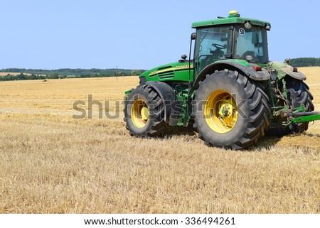 Kalush, Ukraine - August 13: Modern John Deere tractor in the field near the town Kalush, Western Ukraine August 13, 2015 - stock photo