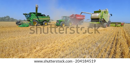 Kalush, Ukraine - AUGUST 7: Modern John Deere tractor with a tank for transportation of grain near the combines harvesting. in the field near the town Kalush, Western Ukraine August 7, 2013.  - stock photo