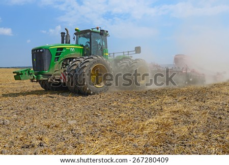 Kalush, Ukraine - August 10 : The modern John Deere tractor performs sowing cereals trailed planter in the field near the town of Kalush, Western Ukraine August 10, 2014 - stock photo