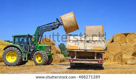 Kalush, Ukraine  - August 8 Unloading bales of straw with a car on the ground floor of a dairy farm near the town of Kalush, Western Ukraine August 8, 2016