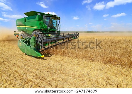 Kalush, Ukraine - July 9: Modern John Deere combine harvesting grain in the field near the town Kalush, Western Ukraine July 9, 2013 - stock photo