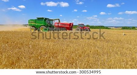 Kalush, Ukraine - July 8: Modern John Deere combine harvesting grain in the field near the town Kalush, Western Ukraine July 8, 2013  - stock photo