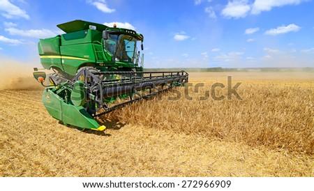 Kalush, Ukraine - July 9: Modern John Deere combine harvesting grain on the field near the town Kalush, Western Ukraine on July 9, 2013  - stock photo