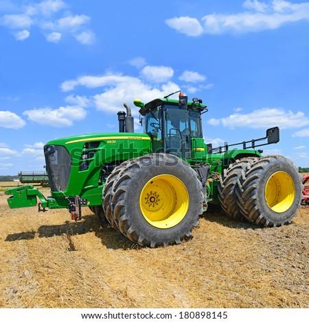 Kalush, Ukraine - July 9: Modern John Deere tractor in the field near the town Kalush, Western Ukraine July 9, 2013 - stock photo