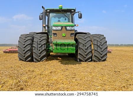 Kalush, Ukraine - July 8: Modern John Deere tractor in the field near the town Kalush, Western Ukraine July 8, 2014 - stock photo