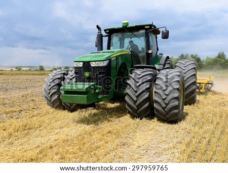Kalush, Ukraine - July 17: Modern John Deere tractor on soil treated cultivator in the field near the town Kalush, Western Ukraine July 17, 2015 - stock photo