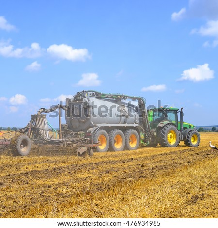 Kalush, Ukraine - July 30: Modern John Deere tractor with a set of equipment for making liquid fertilizer into the soil in the field near the town Kalush, Western Ukraine July 30, 2016