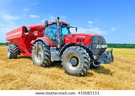Kalush, Ukraine - July 21: Tractor with a tank for transporting grain on the field near the town Kalush, Western Ukraine July 21, 2015